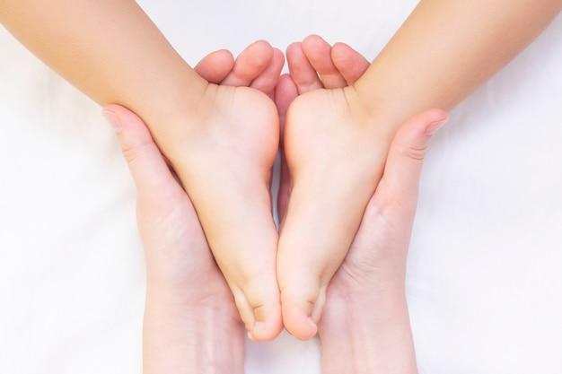 Massagista massageando o pé de uma criança pequena. mãe está fazendo massagem no pé do bebê. prevenção de pés chatos, desenvolvimento, tônus muscular