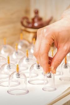 Massagista pega potes de vidro de massagem a vácuo da mesa do spa