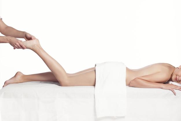 Massagista profissional fazendo massagem nas pernas femininas