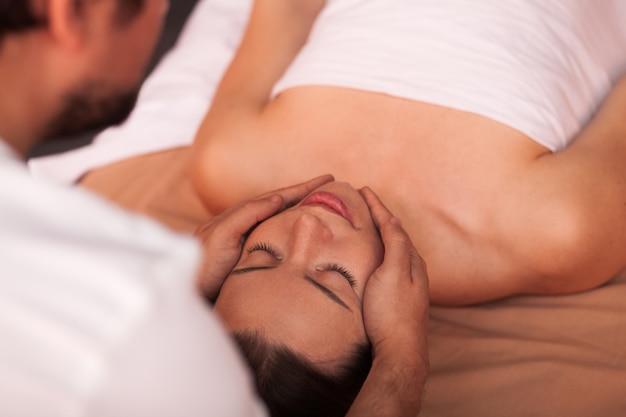 Massagista profissional que executa a massagem da cara e da cabeça no cliente fêmea na clínica da beleza. jovem mulher bonita relaxante, recebendo massagem no centro de spa. recreação, mimos, serviço