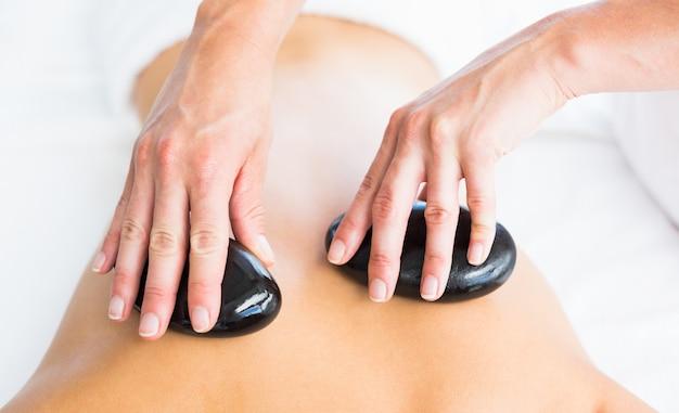 Massagista recortada dando massagem com pedras quentes nas costas da mulher