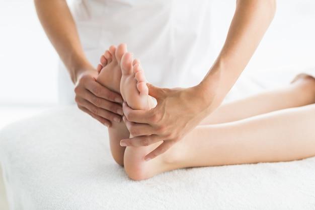 Massagista recortada dando massagem nos pés para mulher