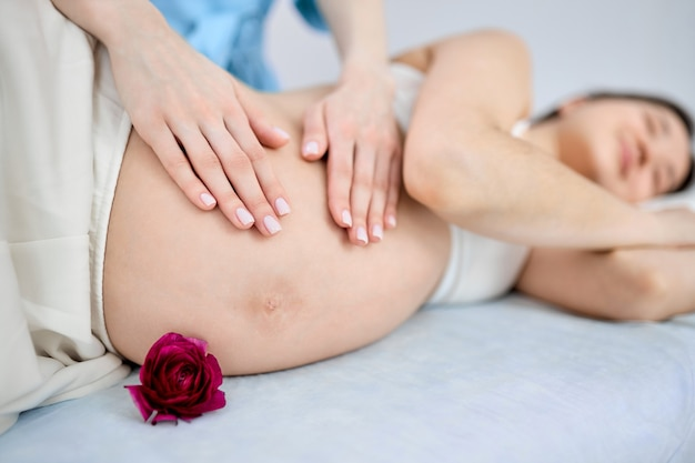 Massagista recortada fazendo massagem para mulher grávida deitada na cama