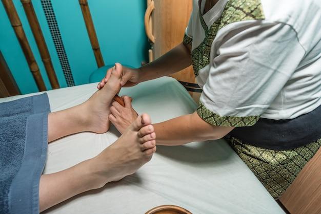 Massagista tailandesa fazendo massagem nos pés de uma menina europeia
