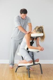 Massagista tratar clientes de volta na cadeira de massagem