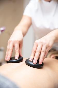 Massagista usando pedras de lava quente durante o spa de saúde relaxante terapia de pedras