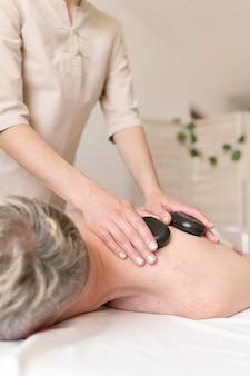 Massagista usando pedras quentes