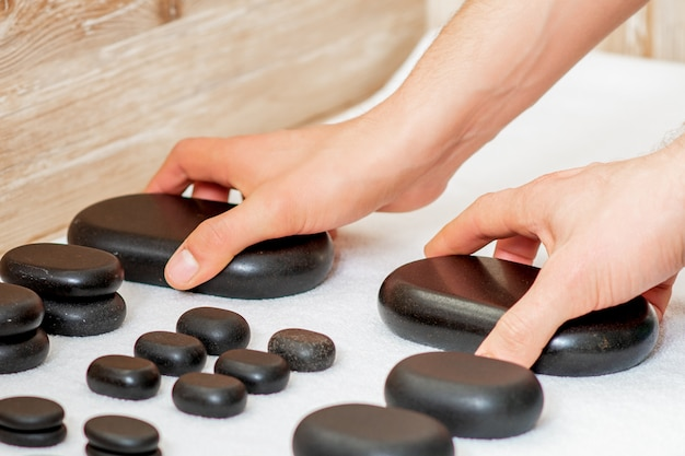 Massagistas tomando pedras quentes de massagem preto