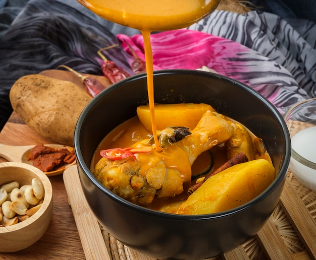 Massaman curry com frango e ervas tailandesas com textura de fundo de madeira