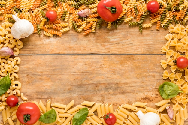 Massas alimentícias não cozidas com tomates; folhas de alho e manjericão dispostas sobre superfície texturizada