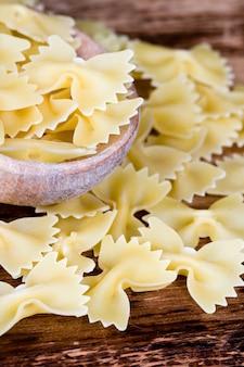 Massas alimentícias não cozidas em colher de pau closeup em fundo de madeira