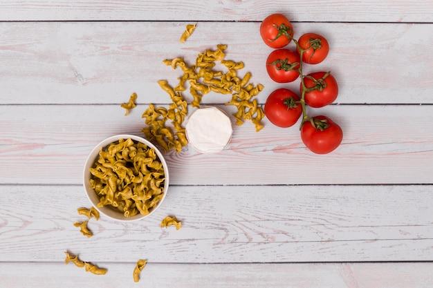 Massas alimentícias não cozidas; tomates vermelhos e recipiente fechado sobre a mesa de madeira