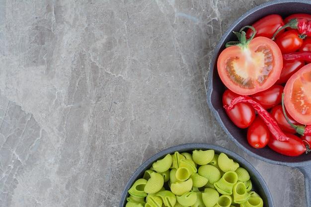 Massas cruas com tomate cereja e pimenta em uma panela preta
