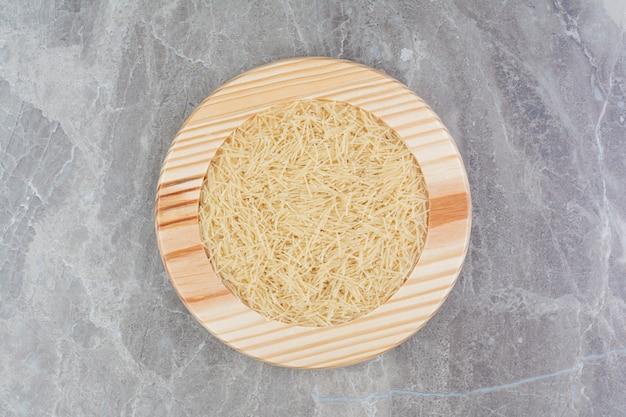 Massas de arroz em travessa redonda de madeira
