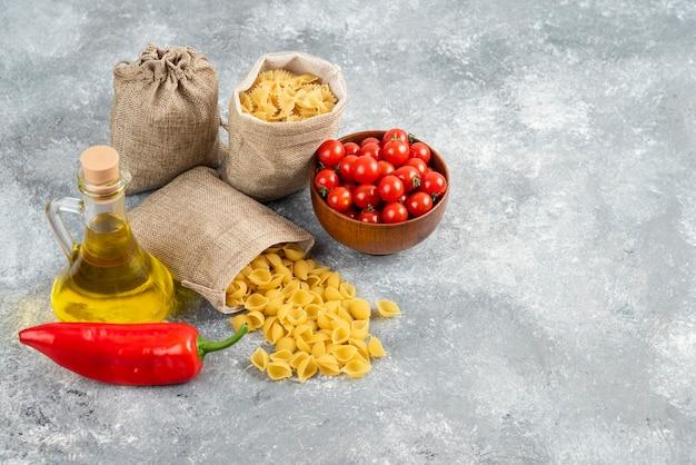 Massas em saquinhos rústicos servidas com tomate cereja, pimenta e azeite.