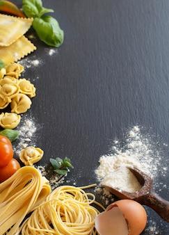 Massas frescas e ingredientes em uma vista superior do quadro escuro