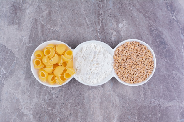 Massas, grãos de trigo e farinha em travessa de cerâmica tripla branca.