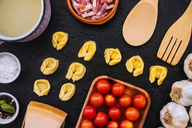 Massas recheadas em meio a ingredientes e utensílios de cozinha
