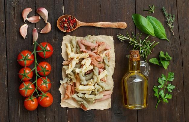 Massas tricolores, vegetais, ervas e azeite de oliva em fundo de madeira