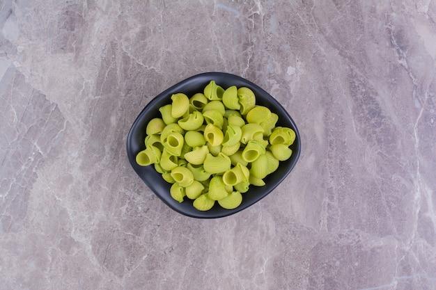 Massas verdes não cozidas em uma tigela de cerâmica no mármore
