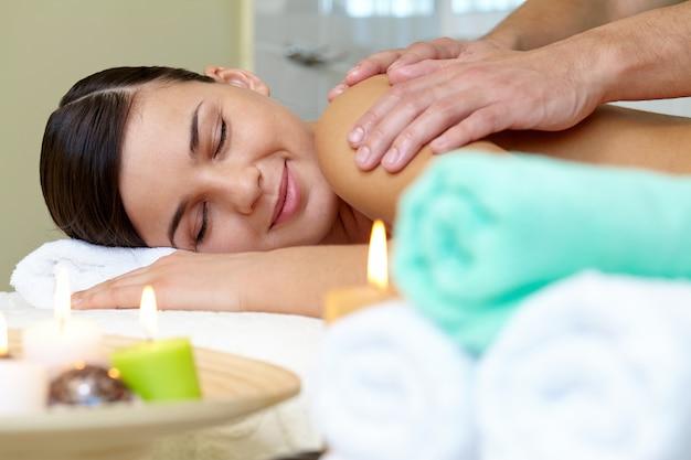 Masseur que faz a massagem no corpo da mulher