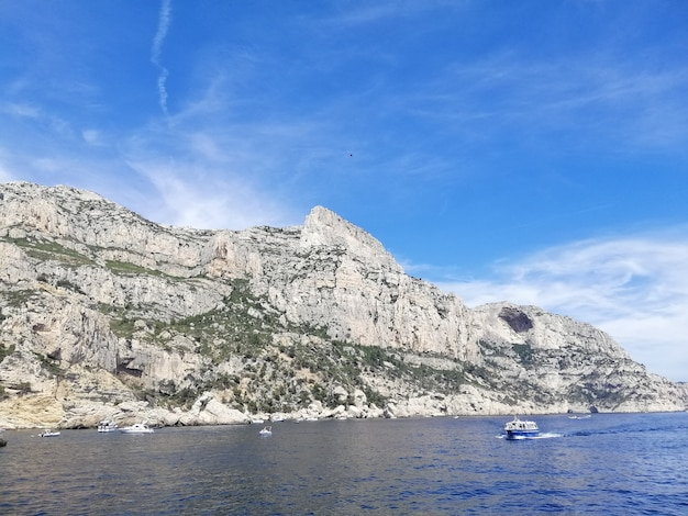 Massif des calanques cercado pelo mar sob um céu azul e luz do sol na frança