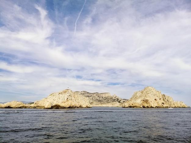 Massif des calanques cercado pelo mar sob um céu nublado e luz do sol em marselha, na frança