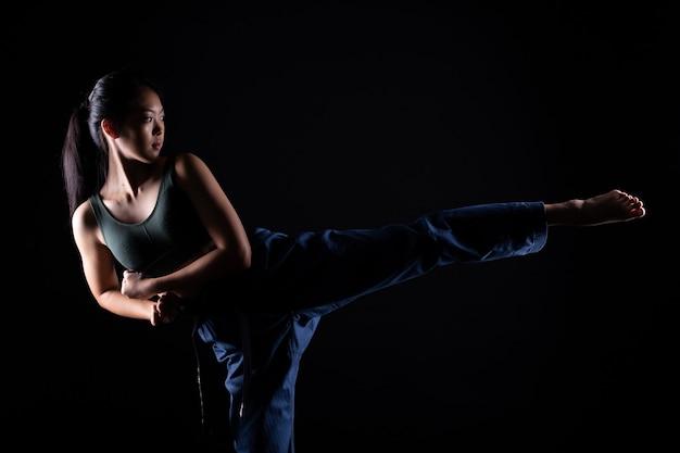 Master black belt taekwondo karate girl que é atleta jovem adolescente mostra poses tradicionais de luta em vestido esporte, parede preta isolada, cópia espaço baixa exposição no escuro