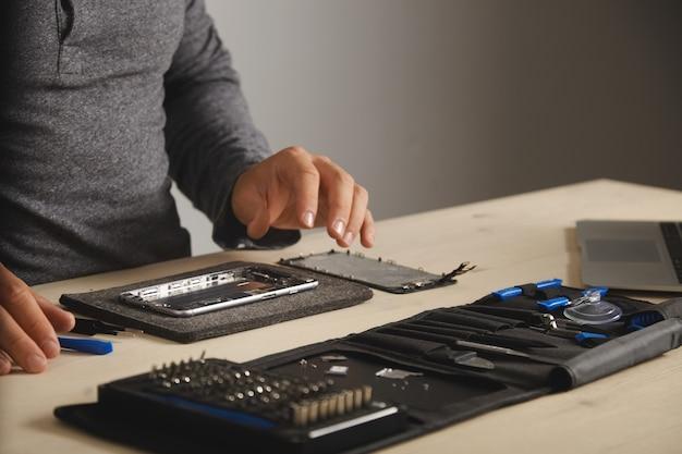 Master está pronto para montar o telefone e consertá-lo com a substituição da bateria e da tela novas, vista lateral