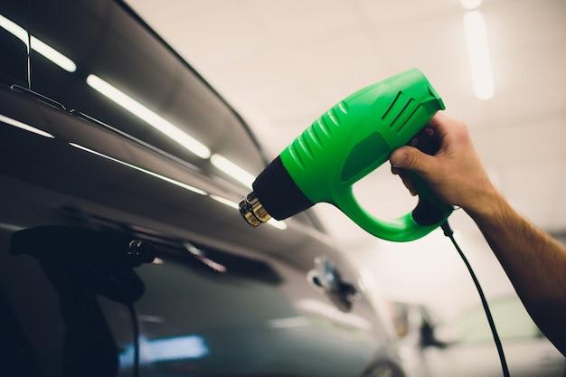 Master instala filme matiz para carro com secador de cabelo. carro de proteção de conceito