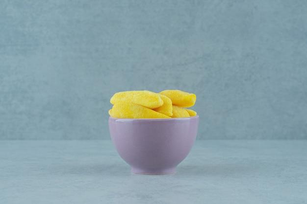 Mastigar bombons em forma de banana em uma tigela na superfície branca