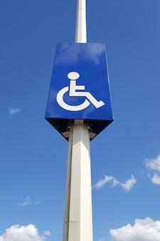 Mastro com sinalização rodoviária e vaga reservada a pessoas com deficiência