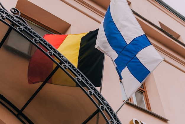 Mastro de bandeira no edifício com a bandeira da finlândia e da bélgica