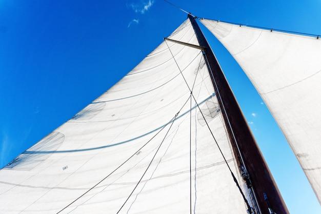 Mastro de um veleiro com equipamento de vela de bermuda contra um céu azul, vista de baixo para cima
