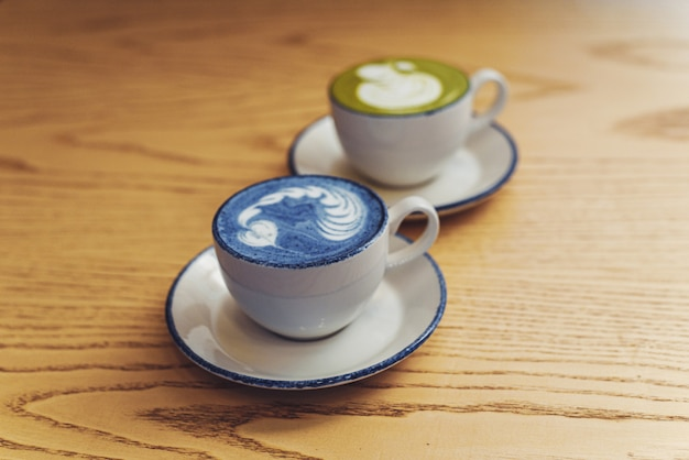 Matcha azul e verde em canecas de cerâmicas brancas em uma mesa de madeira com copyspace