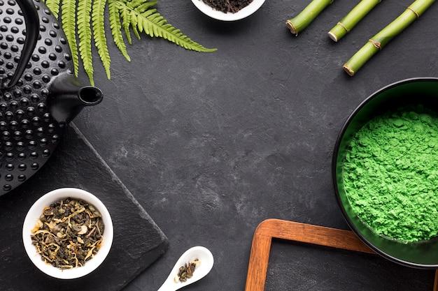 Matcha chá em pó; erva seca; bule de chá; folhas de samambaia e vara de bambu em pano de fundo de pedra ardósia