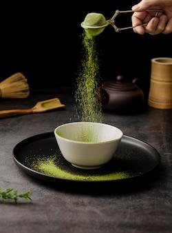 Matcha chá em pó peneirado em tigela