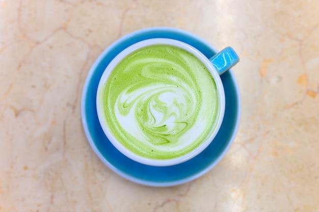 Matcha chá verde com leite com um padrão de espuma de leite em uma xícara de cerâmica azul em cima da mesa