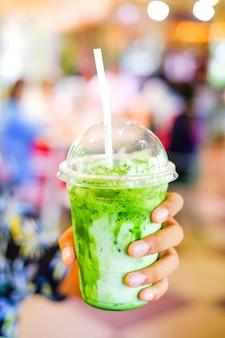 Matcha chá verde com leite de gelo em um copo na mão
