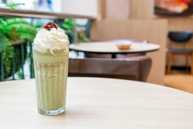 Matcha chá verde com leite misturado com chantilly e feijão vermelho em uma cafeteria e restaurante