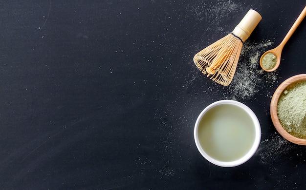 Matcha chá verde com leite na mesa preta