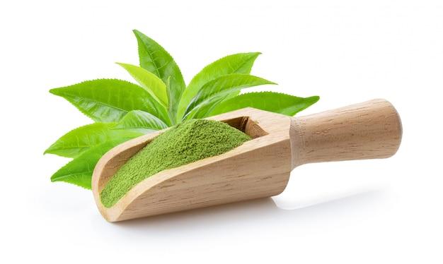 Matcha chá verde em pó na colher de madeira e folhas em branco