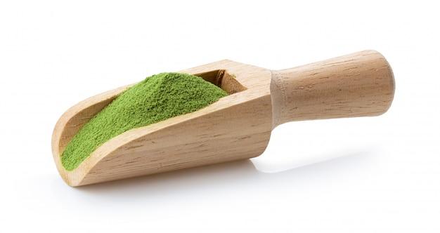Matcha chá verde em pó na colher de madeira em branco