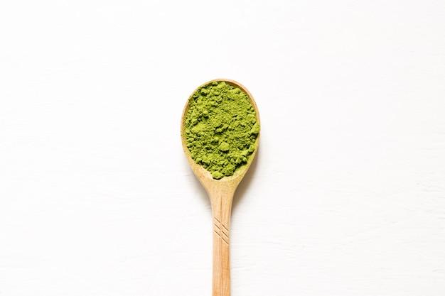 Matcha chá verde pulverizado japonês em uma colher em um fundo branco. vista superior e espaço de cópia.