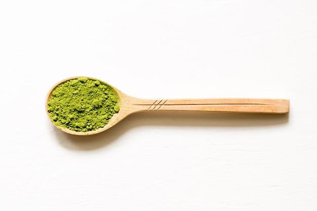 Matcha chá verde pulverizado japonês em uma colher em um fundo branco.