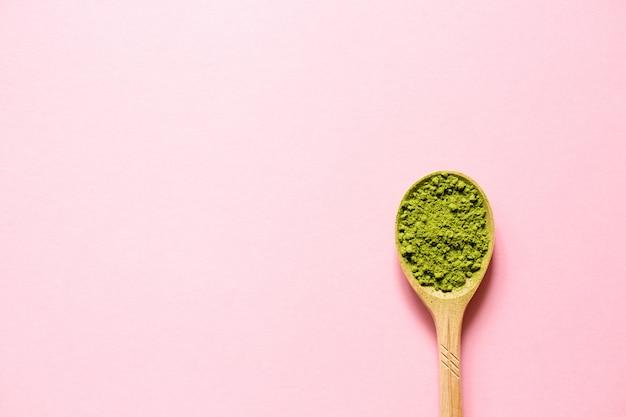 Matcha chá verde pulverizado japonês em uma colher em um fundo cor-de-rosa.