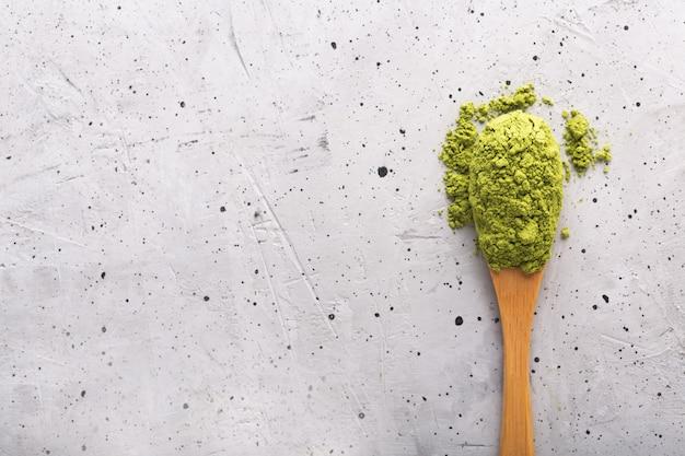 Matcha do chá verde em uma colher na superfície concreta. feche acima do tiro