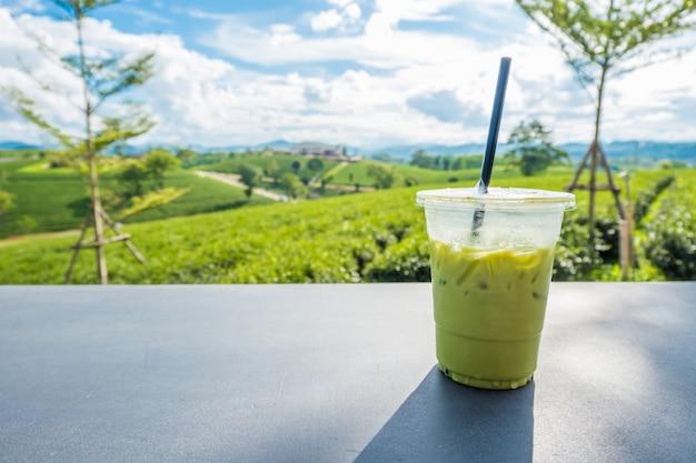 Matcha gelado chá verde em vidro plástico transparente na mesa com fundo de plantação de chá em choui fong