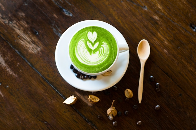 Matcha latte art com grão de café e colher de madeira na mesa de madeira