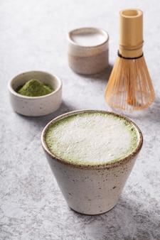 Matcha latte chá verde japonês com leite no fundo branco.